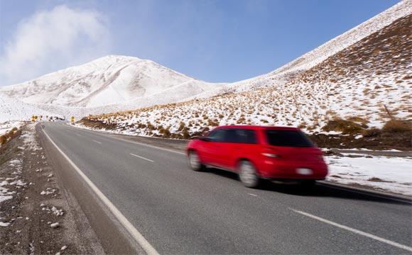 Car driving on road through snowy alpine landscape