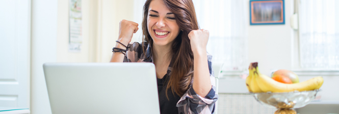 Girl sitting on laptop excited