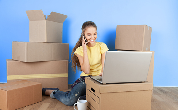 Woman surrounded by boxes looking at laptop on the phone