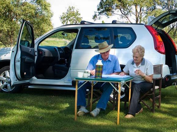 Older couple taking a tea break from a long road trip