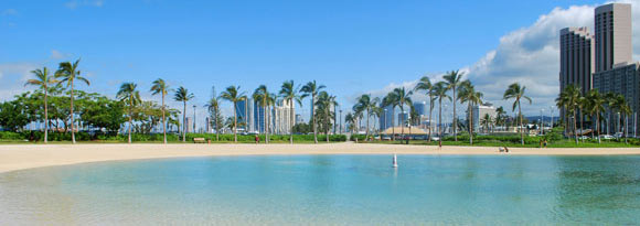 Waikiki Beach, Hawaii with palm trees and buildings in the background