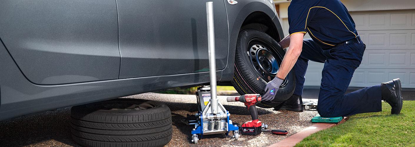 RACQ patrolman changing tyre in member's driveway