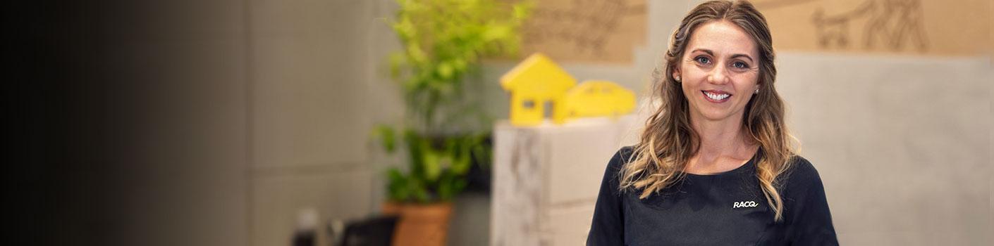 Female RACQ Bank employee smiling in branch